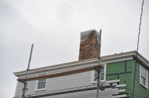 Developers want retroactive approval of changes to this chimney (shown under construction). A local mason says much of it is sooty interior brick
